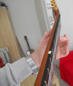 pressing the bottom string against the fretboard